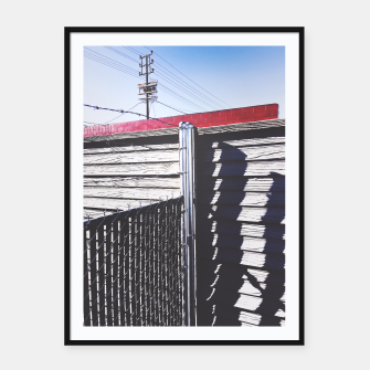 Thumbnail image of steel fence and wooden fence with red building and blue sky background in the city Framed poster, Live Heroes