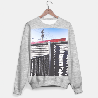 Thumbnail image of steel fence and wooden fence with red building and blue sky background in the city Sweater regular, Live Heroes
