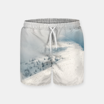 Miniature de image de Clouds clearing above spruce forest and snowy mountains Swim Shorts, Live Heroes